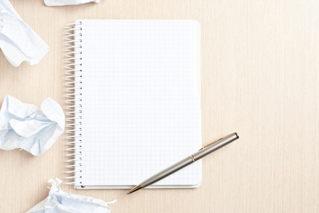 Blank notebook page and crumpled paper wads on desk Stock Photo - 9085014