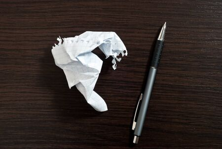 Ripped white paper and pen on dark wooden table Stock Photo - 9085131