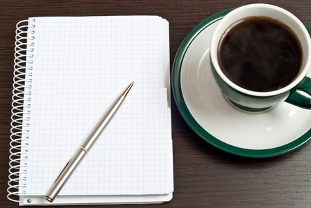 Notebook, silver pen and coffee in green cup on desk photo
