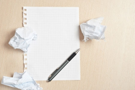 office chaos: Blank notebook page and crumpled paper wads on desk