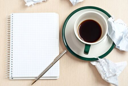 open notebook: Pencil on a white paper with cup of coffee on desk
