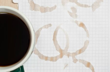 Coffee rings and cup of coffee stains on white paper background photo