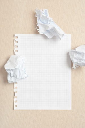 Blank notebook page and crumpled paper wads on desk Stock Photo - 9293391