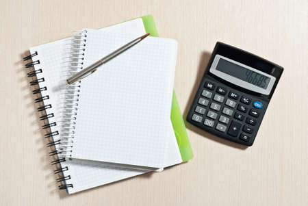 Notebook, ballpen and calculator on wooden desk Stock Photo - 9293394