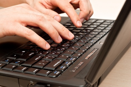 Male hands typing on a laptop keyboard. In motion photo