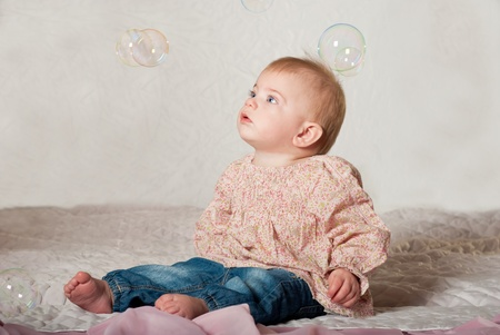 Closeup portrait of little cute baby girl with bubbles photo