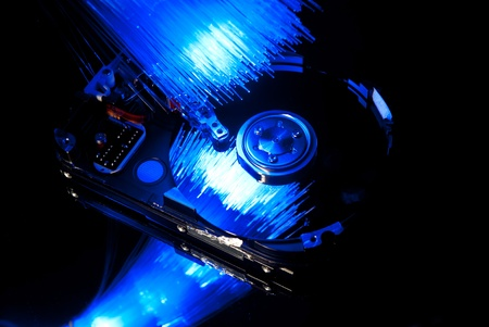 Hard disc with fiber optics background. Studio shot photo