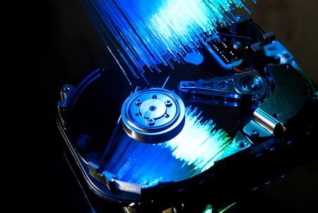 Hard disc with fiber optics background. Studio shot photo