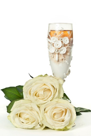 One glass of celebratory champagne with white roses