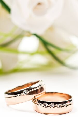 Pair of golden wedding rings with rose bouquet. Macro photo photo