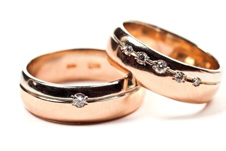Macro photo of gold wedding rings with diamonds. White background. photo