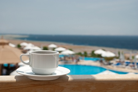 White cup of coffee near sea beach and pools photo