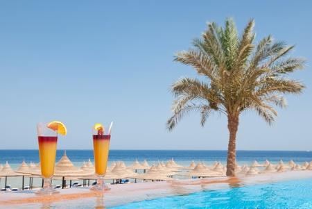 alimentos y bebidas: Dos vasos de cóctel de frutas alcohol en la piscina cerca del mar
