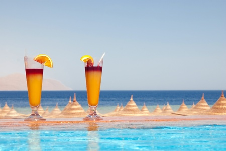 Two glasses of alcohol fruit cocktails at the pool near sea photo