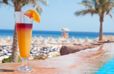 A glass of alcohol fruit cocktail at the pool near sea photo