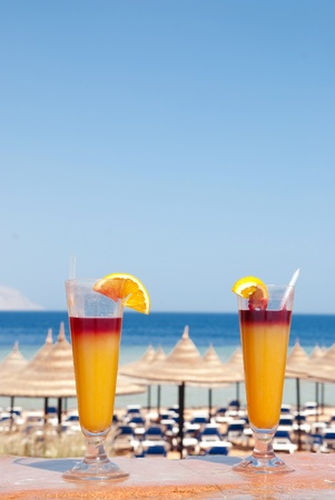 Two glasses of alcohol fruit cocktails at the pool near sea
