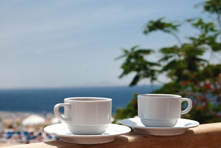 leasure: White cup of coffee near sea beach and pools Stock Photo