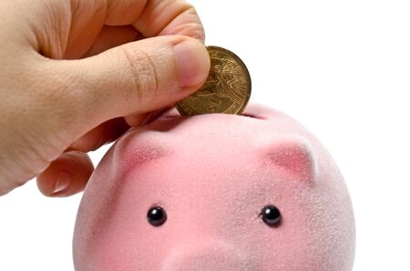 Male hand putting coin into a piggy bank photo