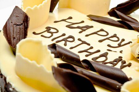 vanilla cake: Chocolate cake with words happy birthday on it