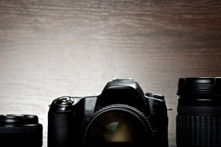 digicam: Black digital camera and two lens. Wooden background Stock Photo