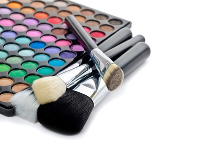 neutrals: Multi colored make-up and brushes isolated on white Stock Photo