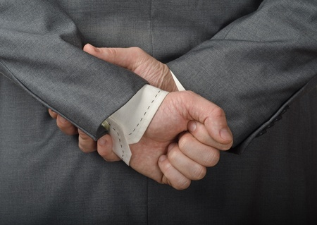 A man in a business suit with his hands behind his back. photo