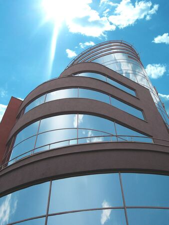 corporate image: The modern building in solar weather, in windows is reflected the blue sky