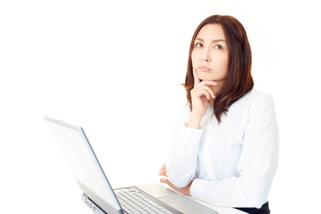 The female office worker who thinks about something in front of a PC Stock Photo - 14879727