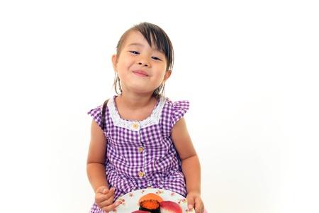 smiling child eating sushi photo