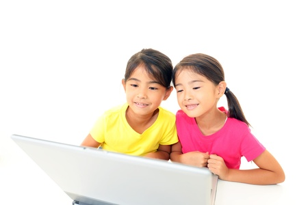 Smiling girls using a laptop photo