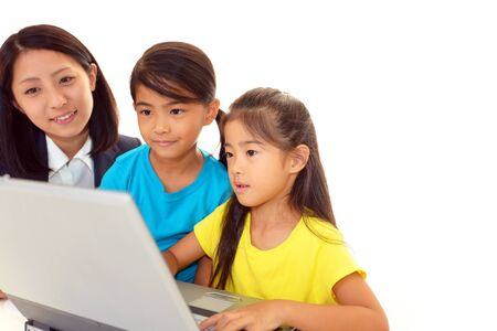 computer lesson: Smiling girls using a laptop Stock Photo