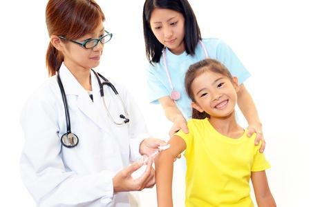 meningococcal: M�dico que den un ni�o una inyecci�n Foto de archivo