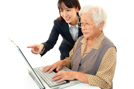 Young woman helping an elderly lady use a computer photo