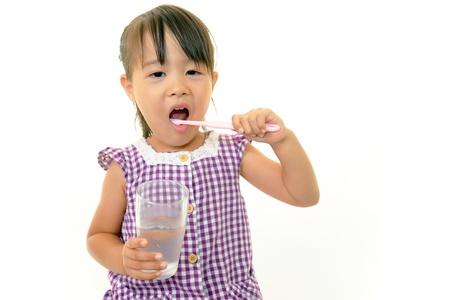 Child brushing her teeth happily photo