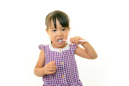 Child brushing her teeth happily photo