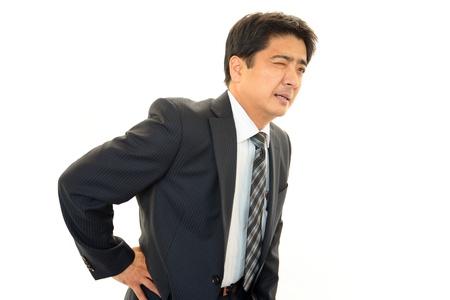 El hombre de negocios que est� preocupado por el dolor de espalda baja