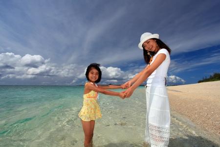 familia jugando: Familia jugando en la playa en Okinawa