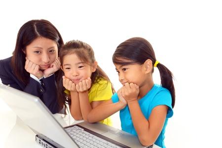 Smiling girls using a laptop 免版税图像