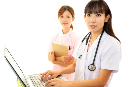 Medical staff working on filling a notepad together Stock Photo - 16884543