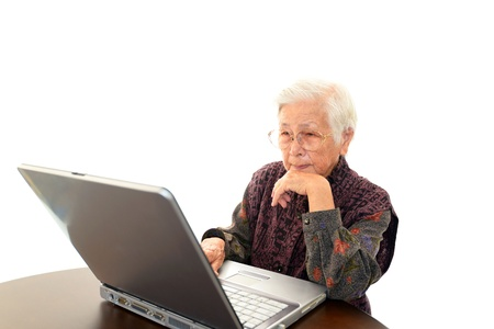 Senior woman with laptop at the desk photo