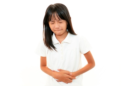 dolor de estomago: La niña que sufre de dolor abdominal Foto de archivo