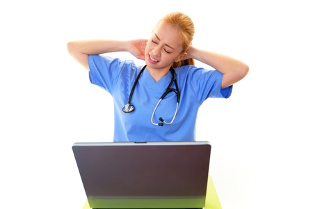Doctor is sitting on her desk and typing on laptop photo