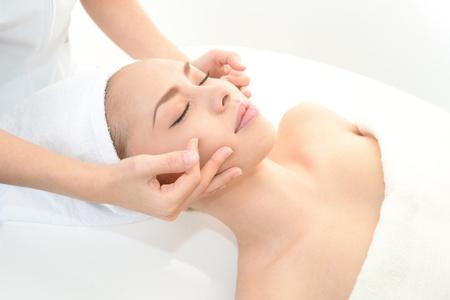facial massage: Jolie femme recevant un massage du visage Banque d'images
