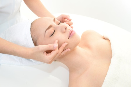 body spa: Pretty woman receiving facial massage