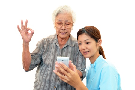 Friendly nurse cares for an elderly woman photo
