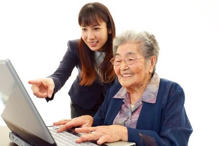 Mujer joven ayudando a una anciana usar una computadora