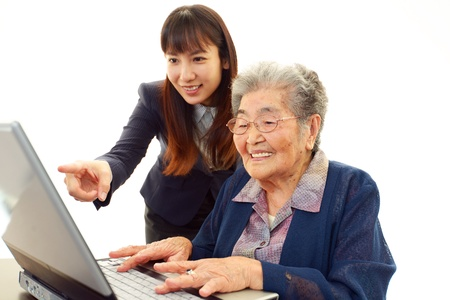 use computer: Young woman helping an elderly lady use a computer