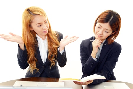dissatisfaction: Two female office worker who express dissatisfaction
