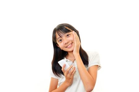 携帯電話を保持している幸せな若い女の子