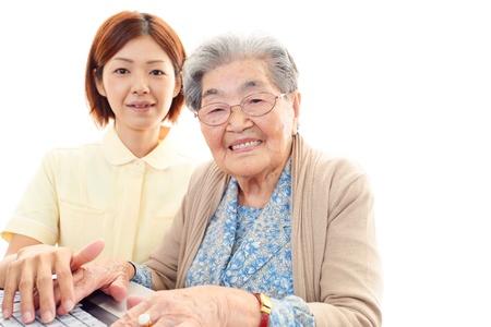 Friendly nurse cares for an elderly woman photo